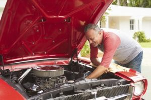 Man works under the hood of his car