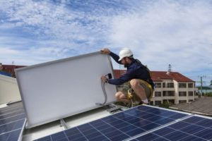 Contstruction worker in hard hat installs solar panel